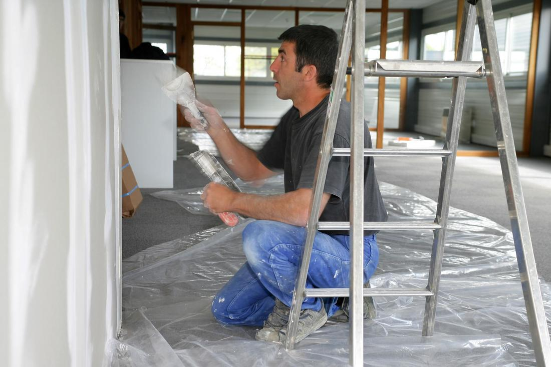 a young man repairing some drywall